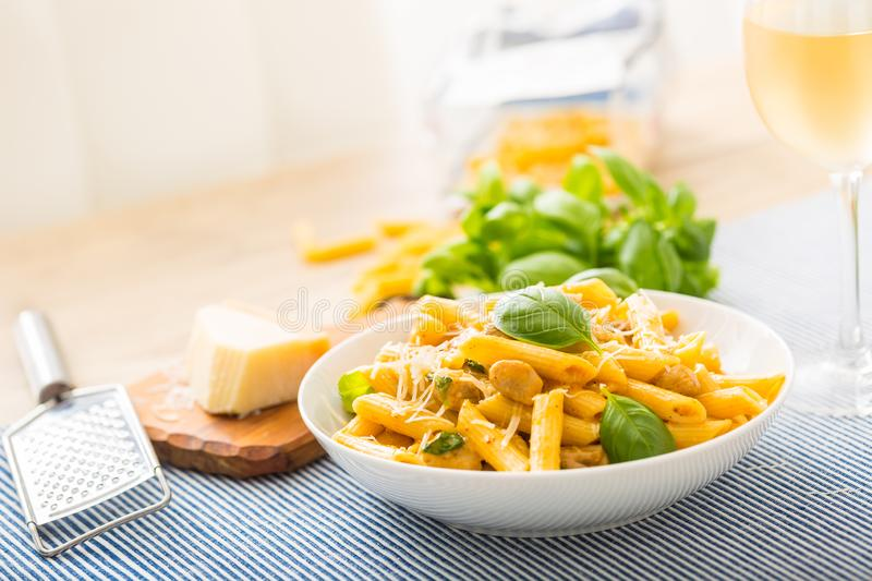 Pasta penne with chicken pieces mushrooms basil parmesan cheese and white wine. Italian food in white plate on kitchen. Pasta penne with chicken pieces mushrooms royalty free stock photography