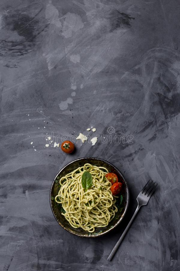 Pasta with pesto and cherry tomatoes at black background, top view stock image