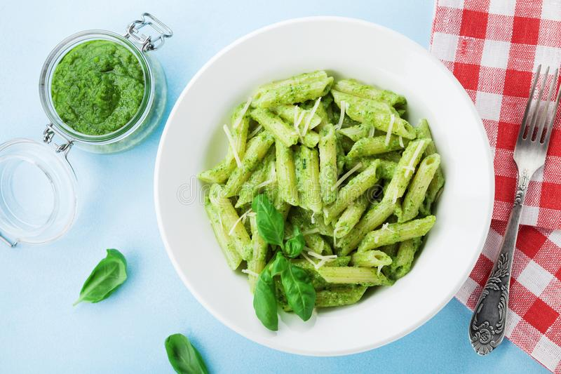 Pasta with pesto sauce decorated basil leaves and cheese in white dish on blue table top view. Traditional italian dinner. royalty free stock photography