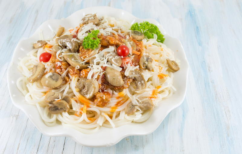 Pasta on a plate with mushrooms. And cherry tomatoes stock images