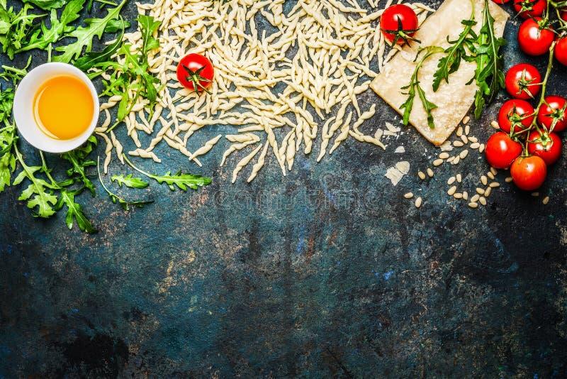 Pasta, pomodori ed ingredienti per la cottura sul fondo rustico, vista superiore, confine immagini stock libere da diritti