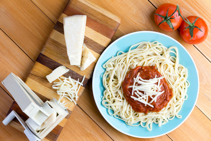 Pasta press with gruyere cheese and spaghetti. Top down first person perspective view on blue plate of spaghetti topped with red sauce and grated gruyere cheese royalty free stock photography