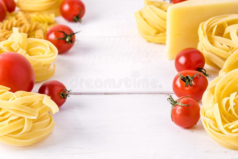 Pasta Products with Tomato Cheese Raw Pasta Fusili Fettuccine Ingredients Italian Food White Background Close Up Copy Space Frame stock images