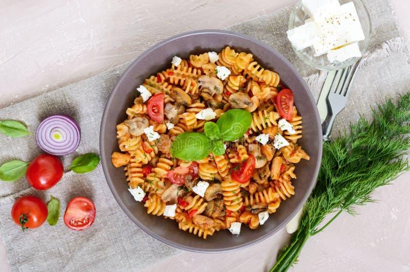 Pasta Radiatori con il pollo, i funghi, i pomodori ciliegia, il feta e la salsa al pomodoro su un fondo leggero immagini stock