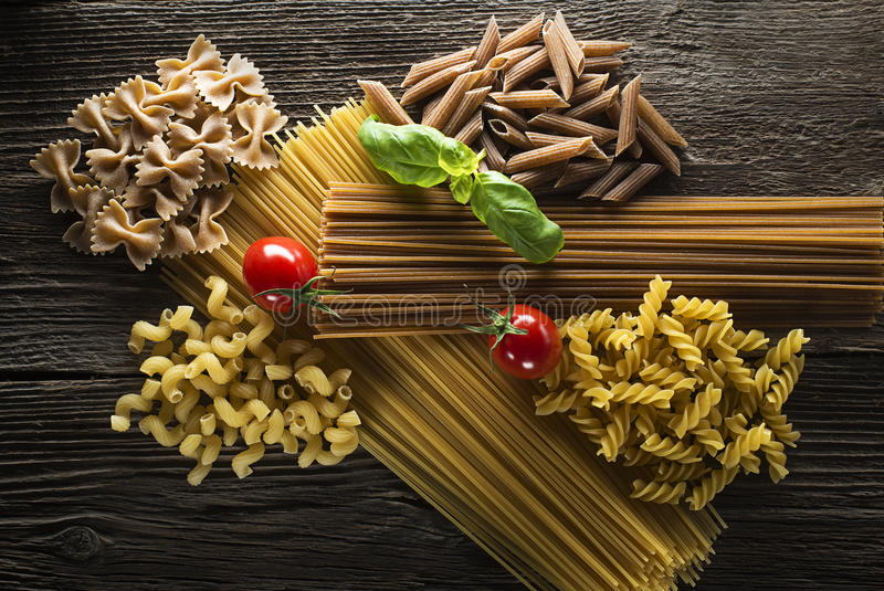 Pasta. Raw pasta with basil and tomato overhead shoot stock image