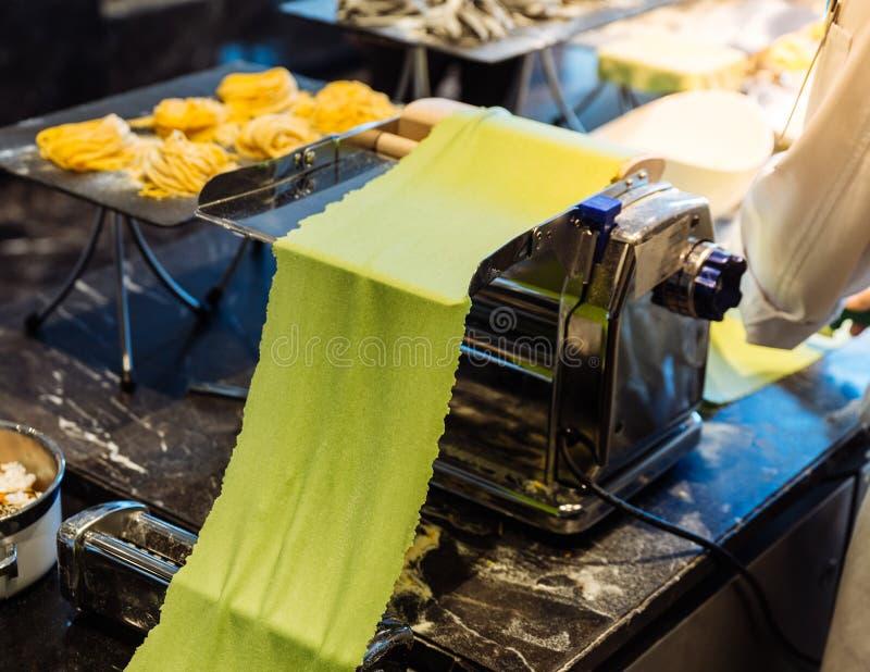 Pasta rodante del cocinero para hacer las pastas frescas hechas en casa del fettuccine de la espinaca imágenes de archivo libres de regalías