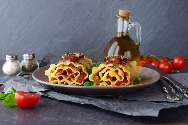 Pasta rolls with vegetables: paprika, onion, olives, mushrooms, tomato, glass jar with olive oil on a light brown plate stock image