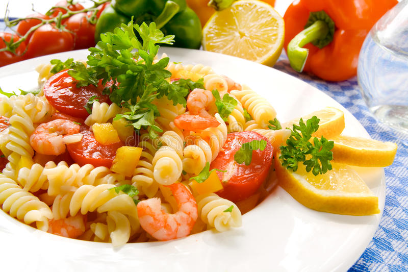 Pasta salad. A white dish with a salad of pasta and prawn stock photo