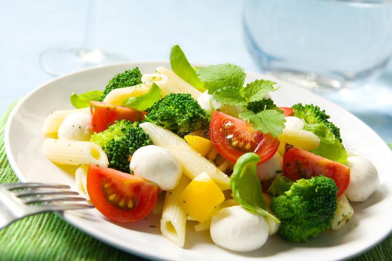 Pasta salad. With small mozzarella balls, broccoli, tomatoes, basil leaves and bell peppers royalty free stock image