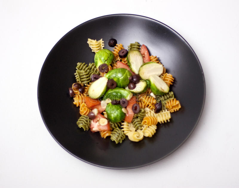 Pasta salad. A pasta salad on a black plate, on a light gray background. Salad contains tomatoes, chopped olives, Brussels sprouts and tri color pasta royalty free stock photography