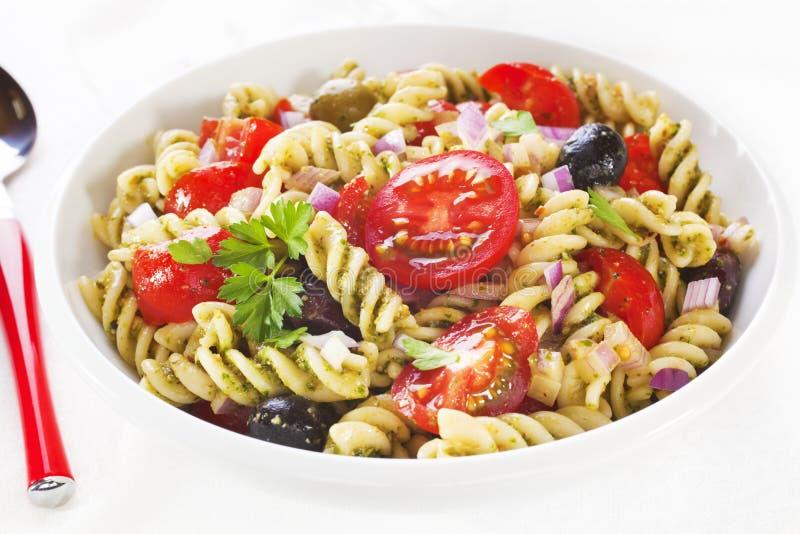 Pasta Salad. Fusili pasta salad, with rocket pesto, juicy tomatoes, olives and onion stock photo