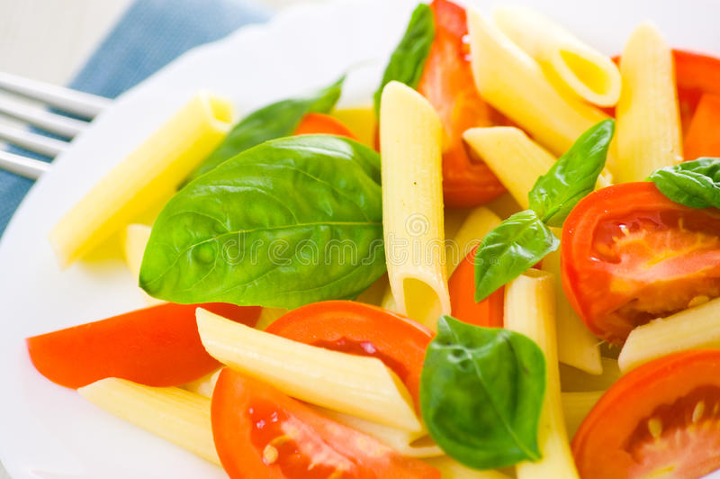 Pasta salad. With tomatoes and fresh basil leaves stock images