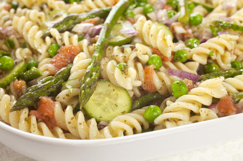 Pasta Salad with Asparagus. Pasta salad made with asparagus, peas, red onion, cucumber and scraps of left over smoked salmon royalty free stock photo