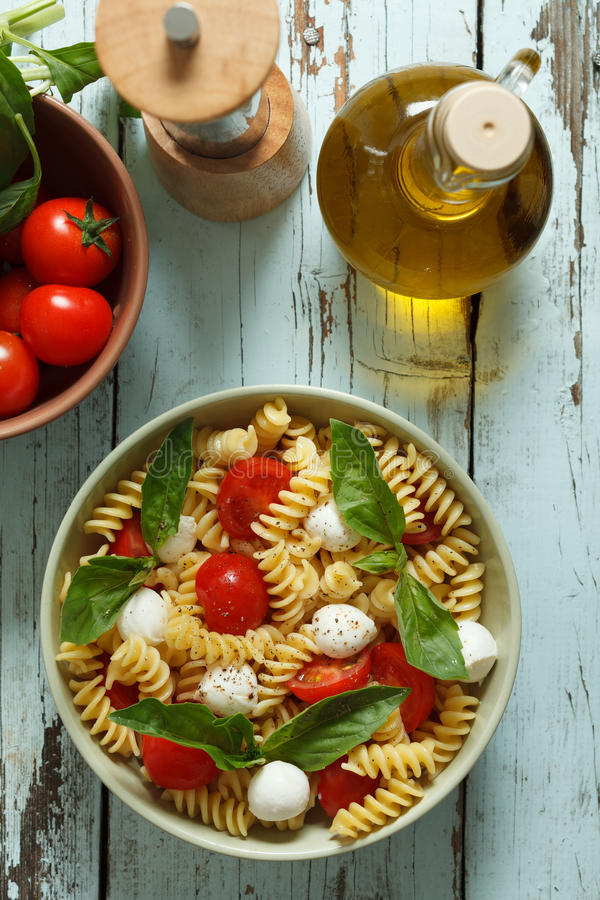 Pasta salad with cherry tomatoes and basil leaves. Pasta salad with cherry tomatoes, basil leaves and mozzarella stock photos