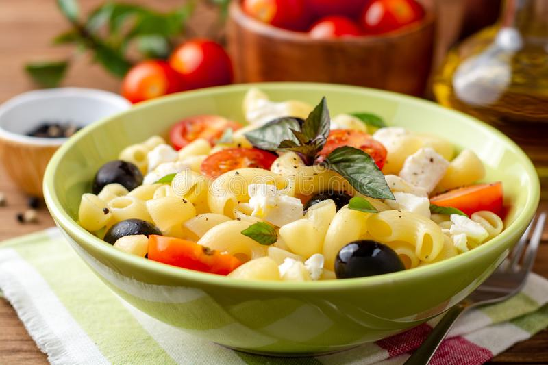 Pasta salad with cherry tomatoes, black olives, feta cheese and basil on wooden background stock photography