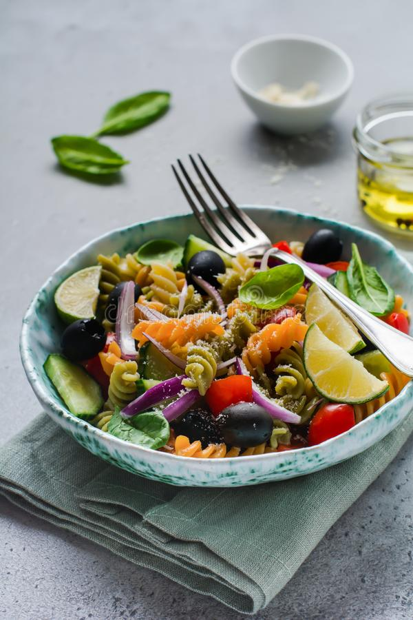 Pasta salad with colorful fusilli and vegetables in a ceramic plate. Top view stock photography