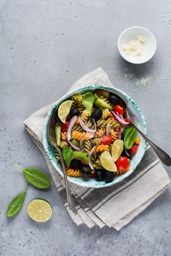 Pasta salad with colorful fusilli and vegetables in a ceramic plate. Top view royalty free stock photos