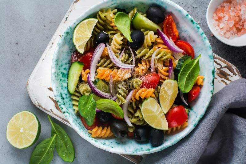 Pasta salad with colorful fusilli and vegetables in a ceramic plate. Top view stock photos