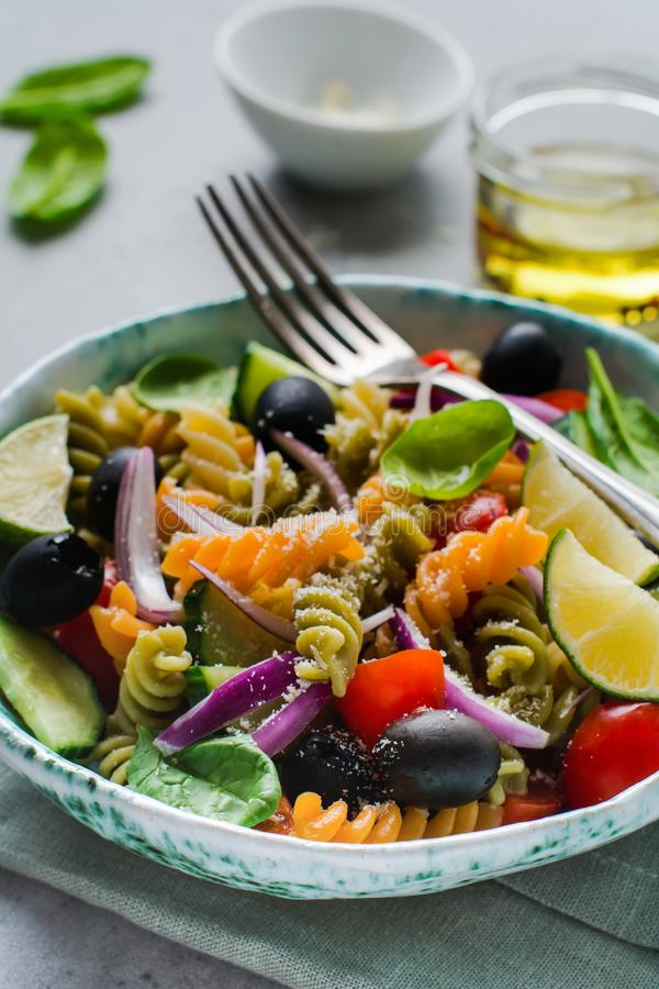 Pasta salad with colorful fusilli and vegetables in a ceramic plate. Top view royalty free stock image