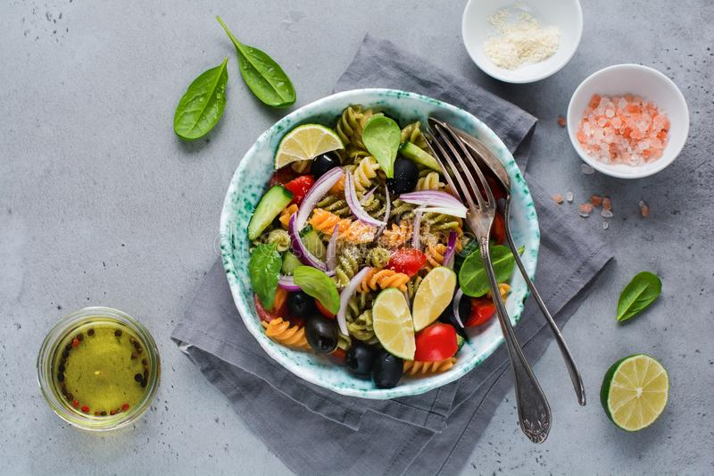 Pasta salad with colorful fusilli and vegetables in a ceramic plate. Top view stock images