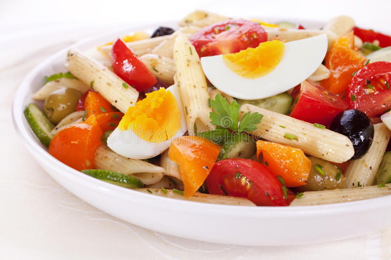 Pasta Salad with Egg. A bowl of pasta salad with egg, tomatoes, cucumber, orange pepper and olives, in a herb dressing stock images