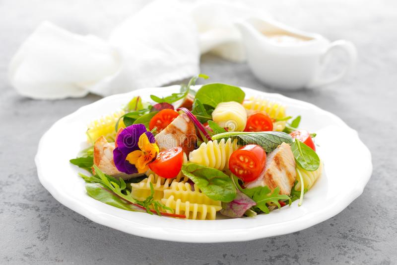 Pasta salad with grilled chicken meat, vegetables and cheese royalty free stock image