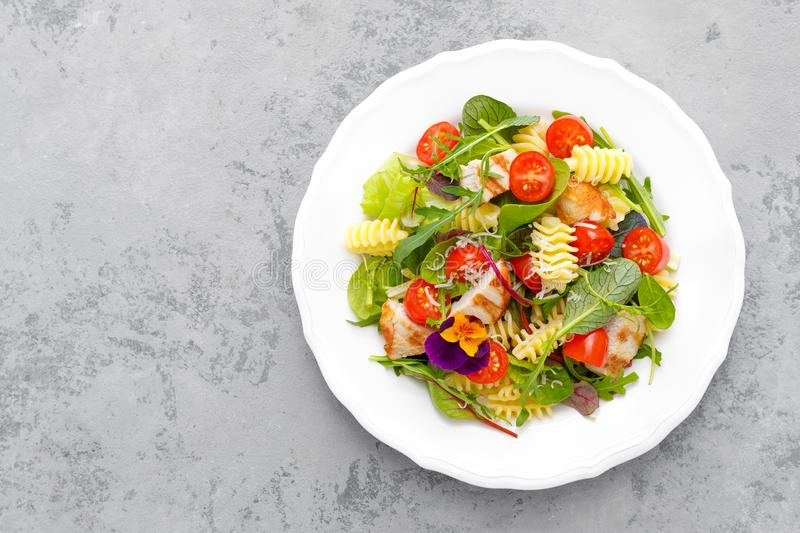 Pasta salad with grilled chicken meat, vegetables and cheese stock image