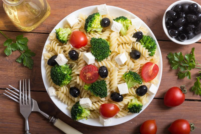 Pasta salad with ingridient. Broccoli , tomatoes , feta and olives royalty free stock photo