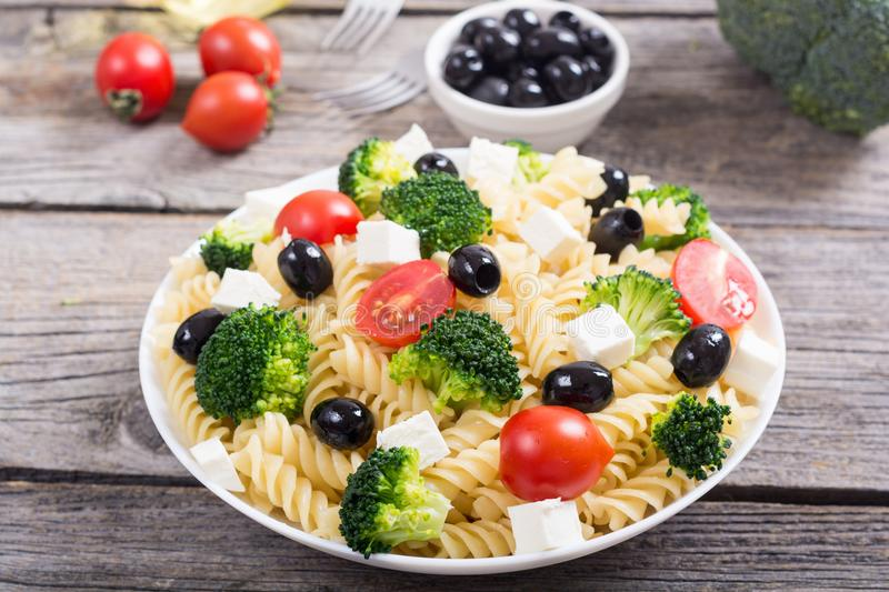 Pasta salad with ingridient. Broccoli , tomatoes , feta and olives stock image