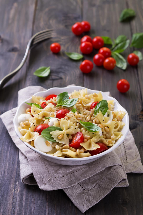 Pasta salad with tomato, mozzarella, pine nuts and basil. In a white ceramic bowl on a wooden table stock images
