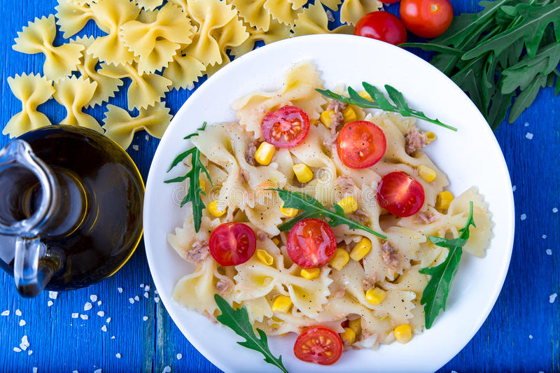 Pasta salad with tomatoes cherry, tuna, corn and arugula on blue wooden background. Top view. stock image