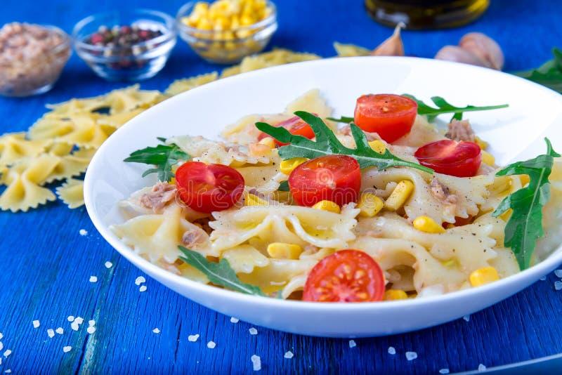 Pasta salad with tomatoes cherry, tuna, corn and arugula. Close up. royalty free stock photography