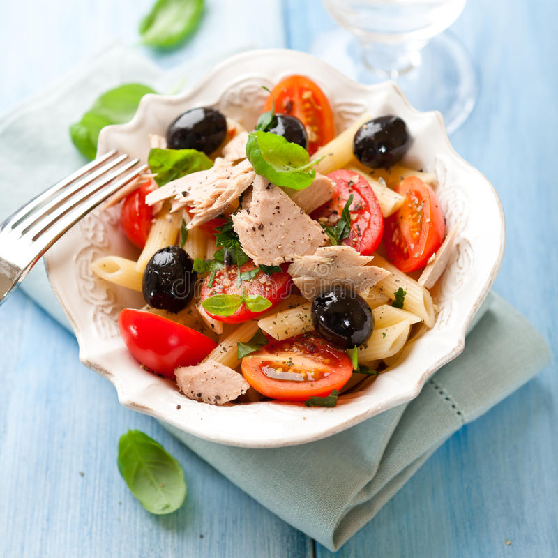 Pasta salad with tuna and olives. Bowl of pasta salad with tuna, olives and cherry tomatoes royalty free stock photo