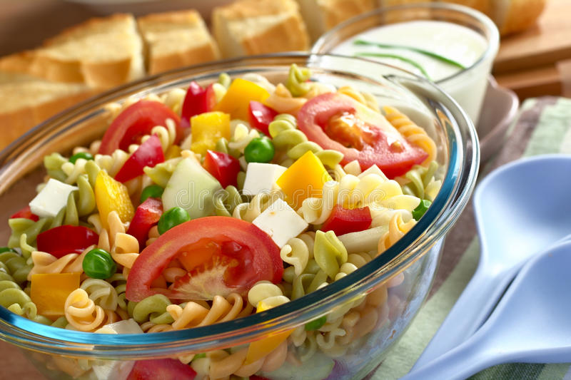 Pasta Salad with Vegetables. Pasta salad with fresh vegetables (tomato, pea, bell pepper, cucumber) and cheese with baguette and salad dressing in the back ( royalty free stock image