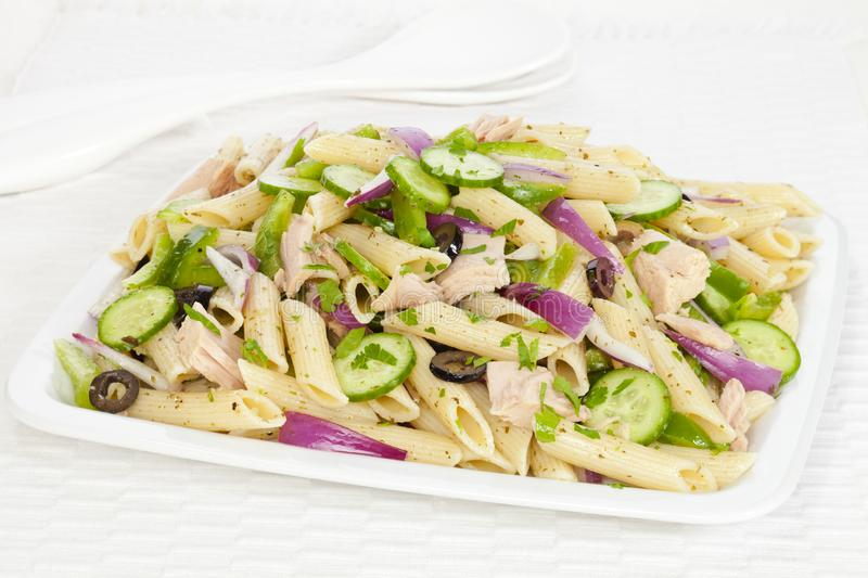 Pasta Salad with Vegetables and Tuna. A pasta salad with a basil pesto dressing, tuna, olives, red onion, cucumber and green pepper, sprinkled with parsley royalty free stock image