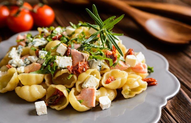Pasta with salmon, sun dried tomato, Feta and Roquefort cheese. Gnocchi pasta with salmon, sun dried tomato, Feta and Roquefort cheese stock image