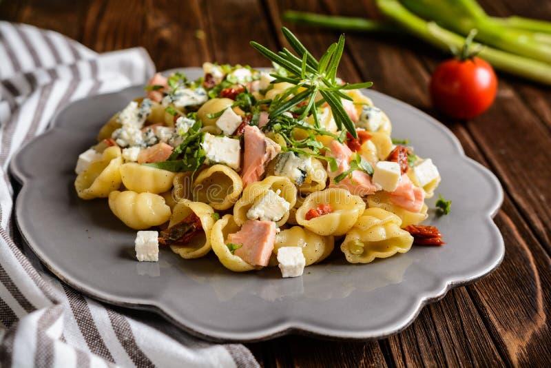 Pasta with salmon, sun dried tomato, Feta and Roquefort cheese. Gnocchi pasta with salmon, sun dried tomato, Feta and Roquefort cheese royalty free stock image