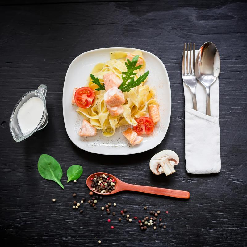 Pasta with salmon and tomato with sauce on black background. Flat lay, top view. Pasta with salmon and tomato with sauce on black background stock image