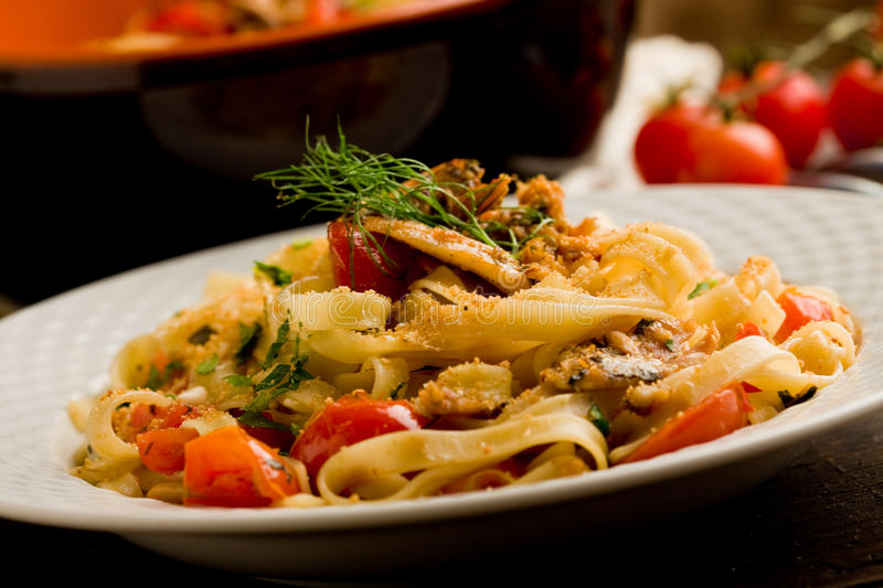 Pasta with Sardines. Italian regional dish made of pasta with sardines on wooden table royalty free stock photo