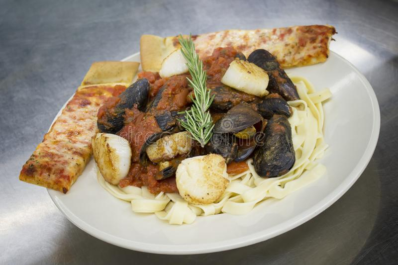 Pasta Seafood Fra Diavolo. Mussels and scallops in red sauce on pasta garnished with garlic sticks stock image