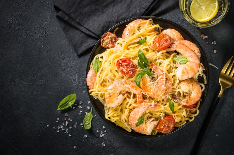 Pasta seafood with shrimp on black table. stock images