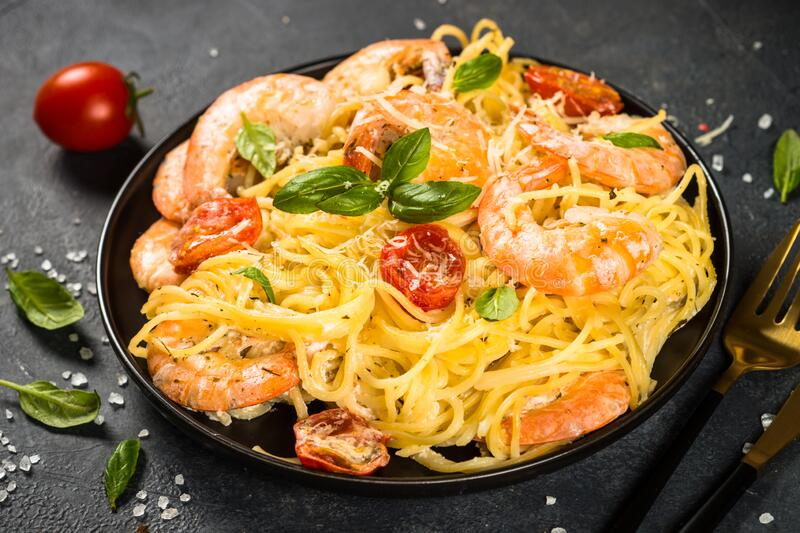 Pasta seafood with shrimp on black table. royalty free stock images