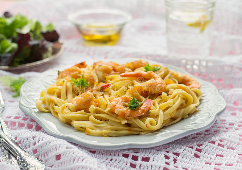 Pasta with shrimps and tomato sauce stock images