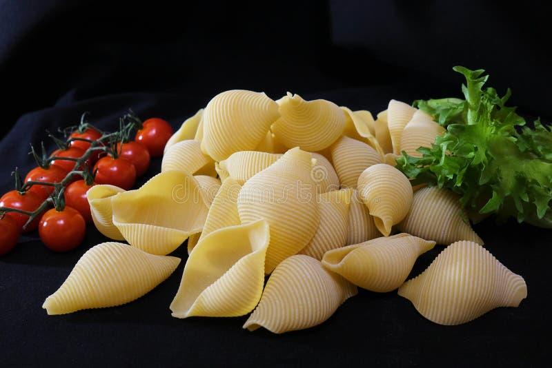 Pasta sotto forma di coperture in una ciotola di legno rotonda con i pomodori ciliegia su un fondo nero Priorità bassa culinaria immagini stock
