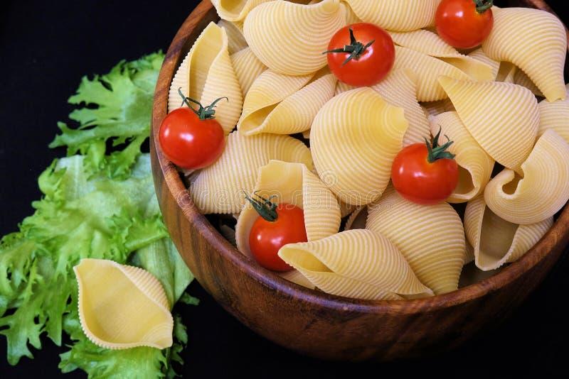 Pasta sotto forma di coperture in una ciotola di legno rotonda con i pomodori ciliegia su un fondo nero Priorità bassa culinaria immagine stock libera da diritti