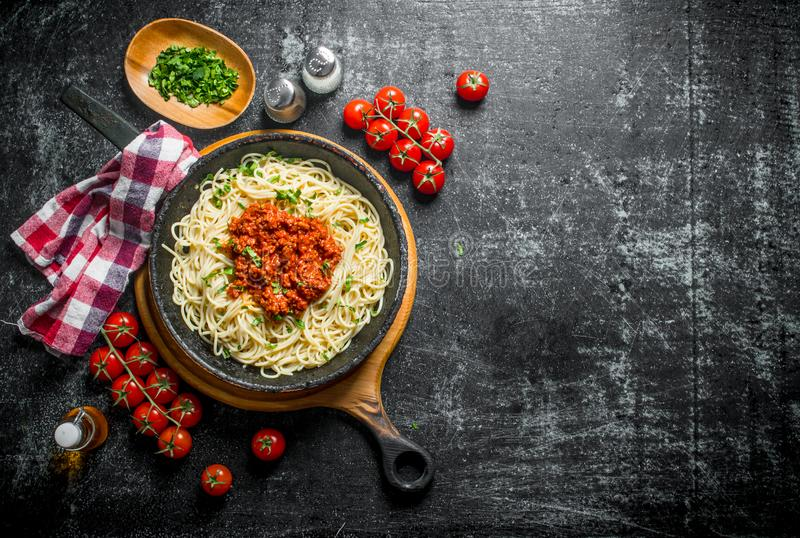Pasta spaghetti with Bolognese sauce in pan with tomatoes,napkin and chopped greens in bowl stock photography