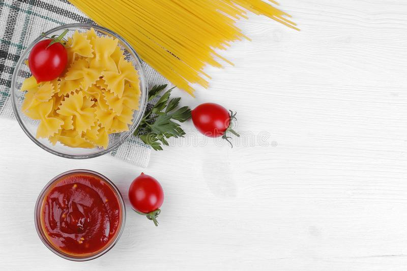 Spaghetti and farfalle with cherry tomatoes, red sauce and parsley on a white wooden background. stock photography
