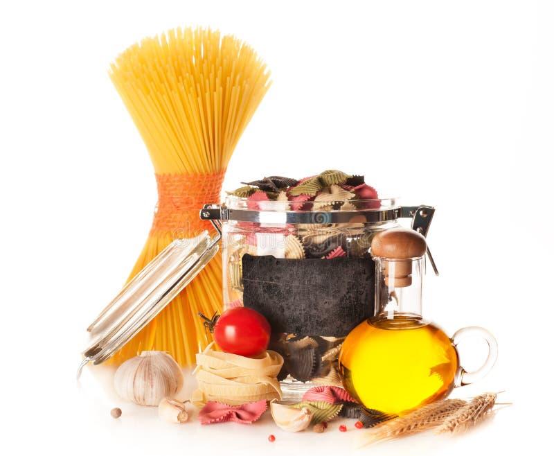 Pasta, spaghetti, farfalle, pomodoro, aglio e spezie italiani su un fondo bianco fotografia stock libera da diritti