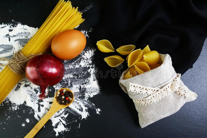 Pasta spaghetti, italian foods concept and menu design, onion, spices on wooden spoon, shells in a bag, raw eggs and flour on a sh stock photos