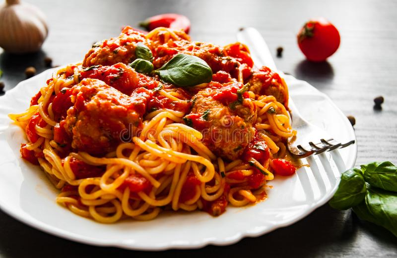 Spaghetti with meatballs in tomato sauce on a plate on dark wooden background stock images